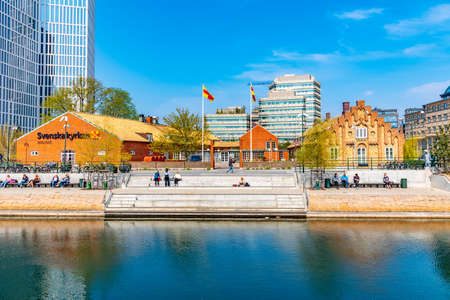 MALMO, SWEDEN, APRIL 25, 2019: People are enjoying a sunny day on waterfront alongside a channel in Malmo, Sweden