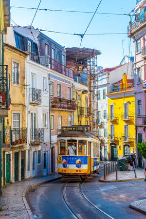 LISBON, PORTUGAL, JUNE 1, 2019: A tram is passing on a narrow street in Lisbon, Portugal