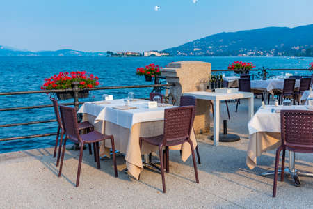Empty tables at a restaurant with view of lago maggiore in italy