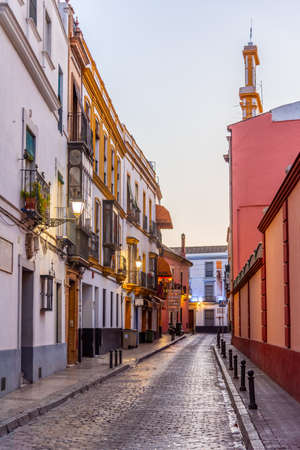 Narrow street in the old town of Sevilla during sunrise, Spain