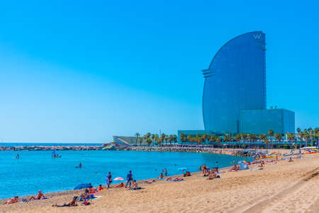 BARCELONA, SPAIN, JUNE 28, 2019: Barceloneta beach in Barcelona dominated by Hotel W designed by Ricardo Bofill, Spain