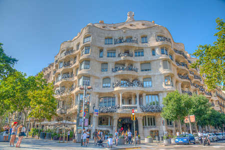 BARCELONA, SPAIN, JUNE 30, 2019: People are passing on a street in front of La Pedrera building in Barcelona, Spain