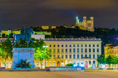 Night view of Basilica Notre-Dame de Fourviere viewed behind statue of Louis XIV in Lyon, France