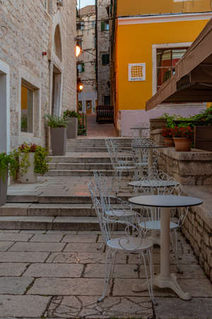 Restaurant tables at a narrow street in the old town of Sibenik, Croatia