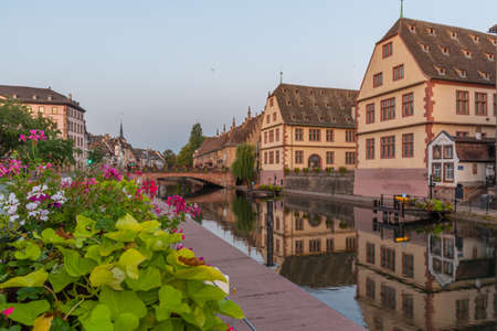 Sunrise view of the waterfront of a channel passing through the old town of Strasbourg, France