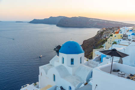 Sunset view of churches and blue cupolas of Oia town at Santorini, Greece