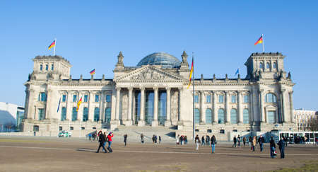BERLIN, GERMANY, MARCH 12, 2015: people are walking in front of the reichstag building in berlin which is the seat of the german parliament.