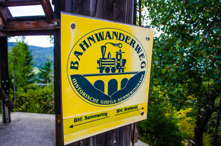 SEMMERING, AUSTRIA, OCTOBER 3, 2015: sign showing direction of the yellow tourist path on the semmeringbahn track in Austria Editorial