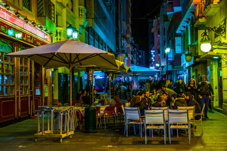 ALICANTE, SPAIN, JANUARY 2, 2016: View of a narrow street in the historical center of spanish city alicante where local people enjoy nightlife in front of many bars. Editorial