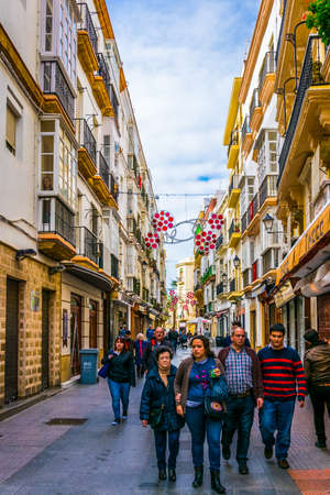 CADIZ, SPAIN, JANUARY 6, 2016: people are stolling through a narrow street in historical center of spanish city cadiz