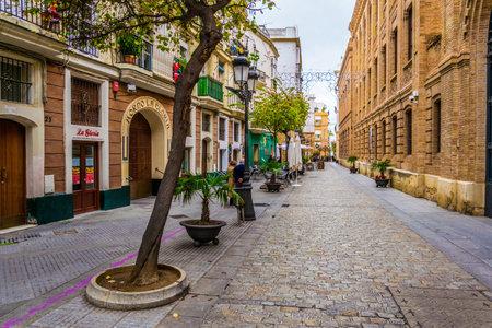 CADIZ, SPAIN, JANUARY 6, 2016: people are stolling through a narrow street in historical center of spanish city cadiz