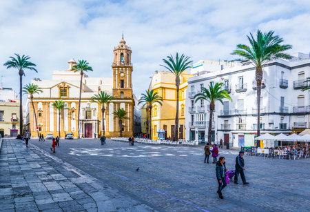 CADIZ, SPAIN, JANUARY 6, 2016: people are crossing plaza de la catedral in front of the church of santiago in spanish city cadiz 新闻类图片