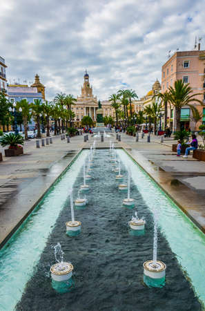 CADIZ, SPAIN, JANUARY 6, 2016: View of a fountain situated on the square of saint john of god in cadiz with town hall on background