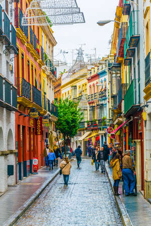 SEVILLA, SPAIN, JANUARY 7, 2016: people are stolling through a narrow street situated in the center of the spanish city sevilla