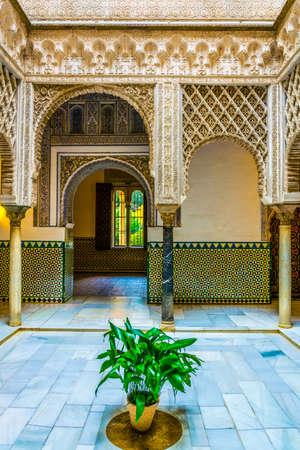 SEVILLA, SPAIN, JANUARY 7, 2016: View of a courtyard with a flower, decorated with yellow and white tiles in the royal alcazar palace in the spanish city sevilla