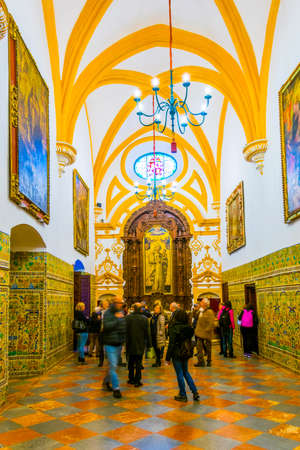 SEVILLA, SPAIN, JANUARY 7, 2016: a group of tourist is admiring a decorated chamber of the real alcazar palace in the spanish city sevilla.