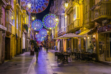 CADIZ, SPAIN, JANUARY 6, 2016: people are stolling over calle ancha street in historical center of spanish city cadiz during night