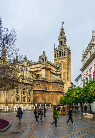 SEVILLA, SPAIN, JANUARY 7, 2016: a group of tourists is passing by under the la giralda tower in the spanish city sevilla