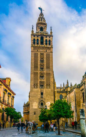 SEVILLE, SPAIN, JANUARY 7, 2016: people are strolling in front of the la giralda tower in the spanish city sevilla
