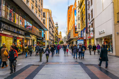 MADRID, SPAIN, JANUARY 9, 2016: People are walking through a narrow street leading to the puerta del sol square in the spanish capital madrid