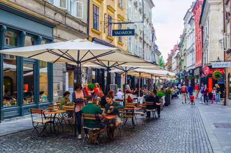 LJUBLJANA, SLOVENIA, JULY 29, 2015: View of the stari trg street in slovenian capital ljubljana, which stretches thourgh the heart of the old town and is full of restaurants.