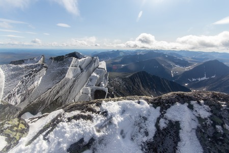 snowy rocks in the foreground and the huge mountain in the background in the mountains of the Subpolar Urals