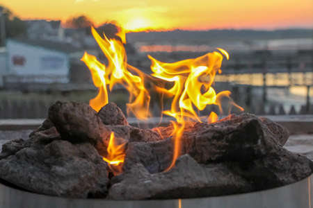 Fire burning in a pit at sunset Imagens