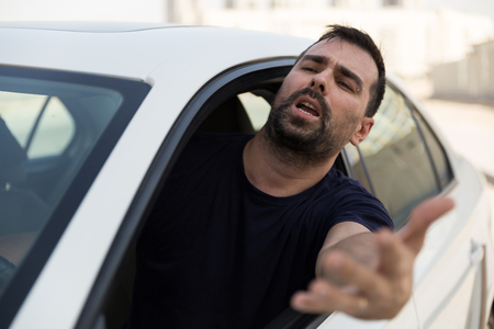 Angry driver pissed off by drivers in front of him and gesturing with hands. Road rage traffic jam concept.  Angry man driving a vehicle is expressing his road rage. Banco de Imagens