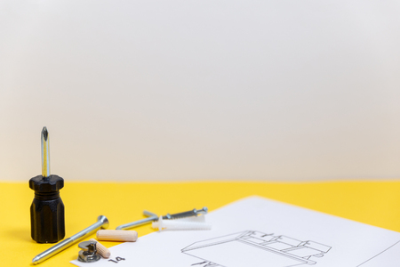 Group of equipment for furniture assembly on yellow board with space for text.