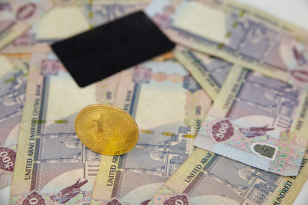Bitcoin token on top of Dubai, dirham banknotes money with black credit card. Cryptocurrency versus paper currency versus credit card concept Stock fotó