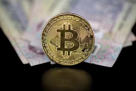 Bitcoin token on black with reflection, on top of Dubai, dirham banknotes money. Cryptocurrency versus paper currency concept