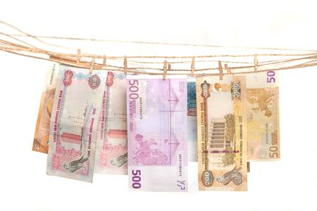 Euro and dirham banknotes hanging on a rope with clothespin. Money laundering concept. Banco de Imagens