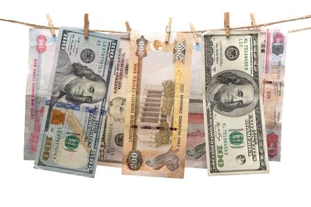 Dirham and dollar banknotes hanging on a rope with clothespin. Money laundering concept. Stock fotó
