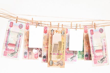 Dirham banknotes hanging on a rope with two blank bank cards between them. Money versus credit/debit card concept. Stock Photo