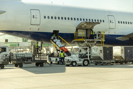 Loading - unloading bags, luggage and to/from an airplane in airport. No logo or faces visible. Airplane lavatory service emptying the tanks.