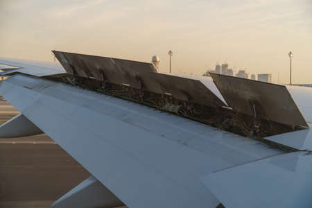 View from the passenger window - Wing of an airplane landing above the runway at high speed during the sunset with flaps raised