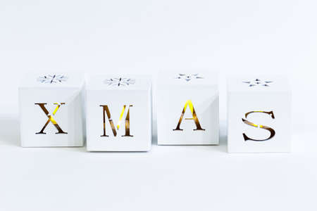 White Wooden cubes with candle light inside spelling the word xmas on white background. Christmas composition. Christmas, winter, new year concept. Flat lay, top view, copy space.