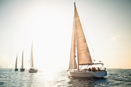 bow of boat: Sailing ship yachts with white sails in a row Stock Photo