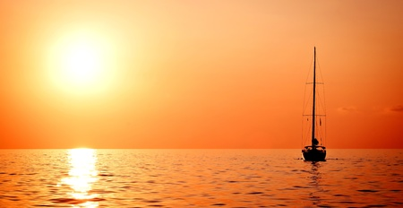 bow of boat: Lonely yacht at sunset Stock Photo
