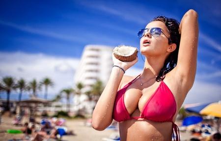 tetas: Mujer joven sosteniendo caliente de coco