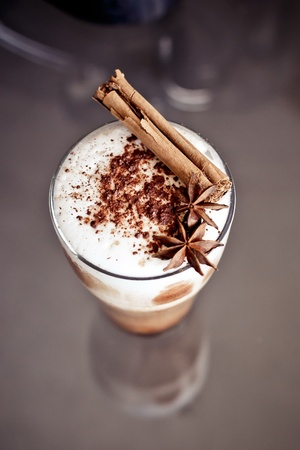 Latte macchiato with cinnamon and anise stars on the table photo