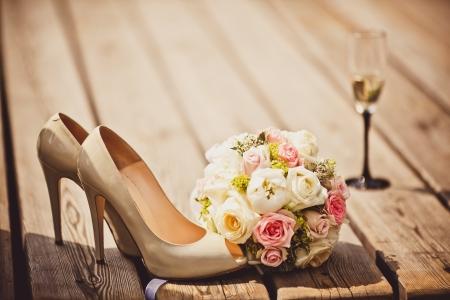Close-up van huwelijksboeket en bruid schoenen