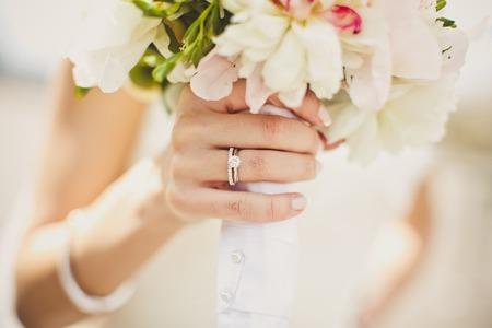 ring engagement: Cerca de las manos de la novia con flores