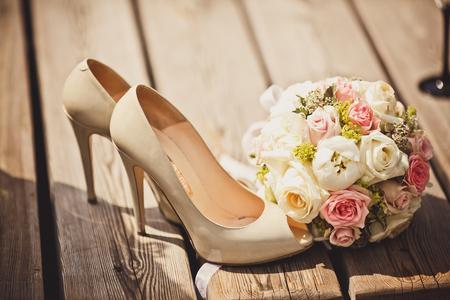 Close-up van bruiloft boeket en bruid schoenen