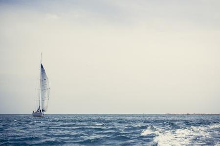 Yacht à voile avec voiles blanches en pleine mer