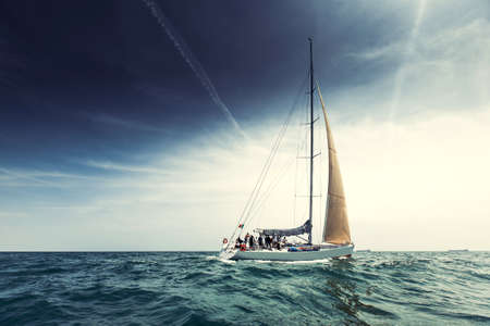 speed boat: Sailing ship yachts with white sails in the open sea