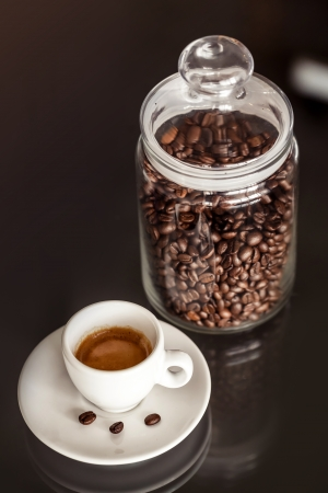 Jar of coffee and cup of black espresso on the table photo