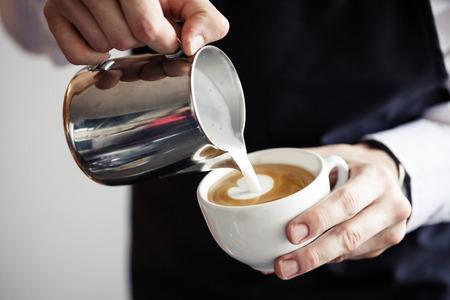 Close-up van Barman het maken van koffie, melk gieten