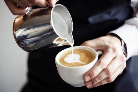 serve: Closeup of Barman making coffee, pouring milk