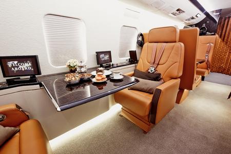 modern interieur: Prive vliegtuig interieur met houten tafels en lederen zetels